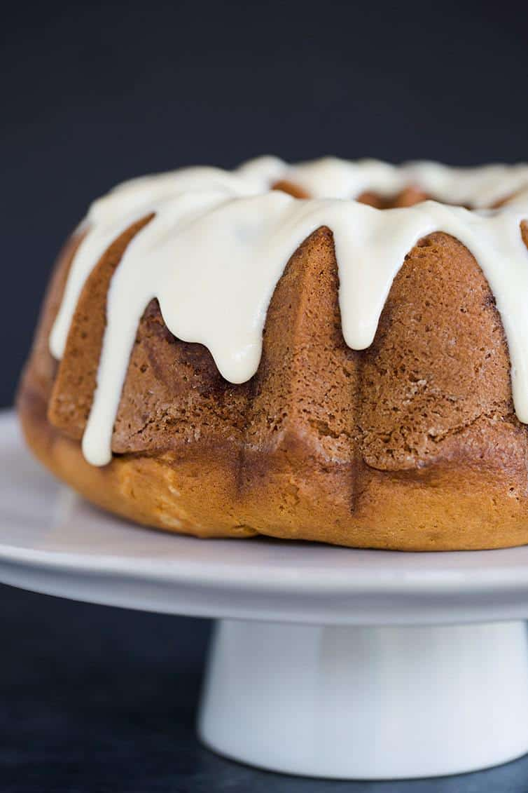 cinnamon coffee cake baked in a bundt pan covered in cream cheese icing