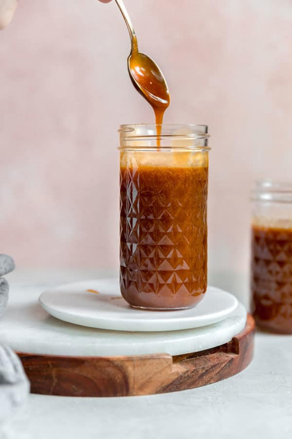 A jar of salted caramel sauce with a spoon scooping some out.
