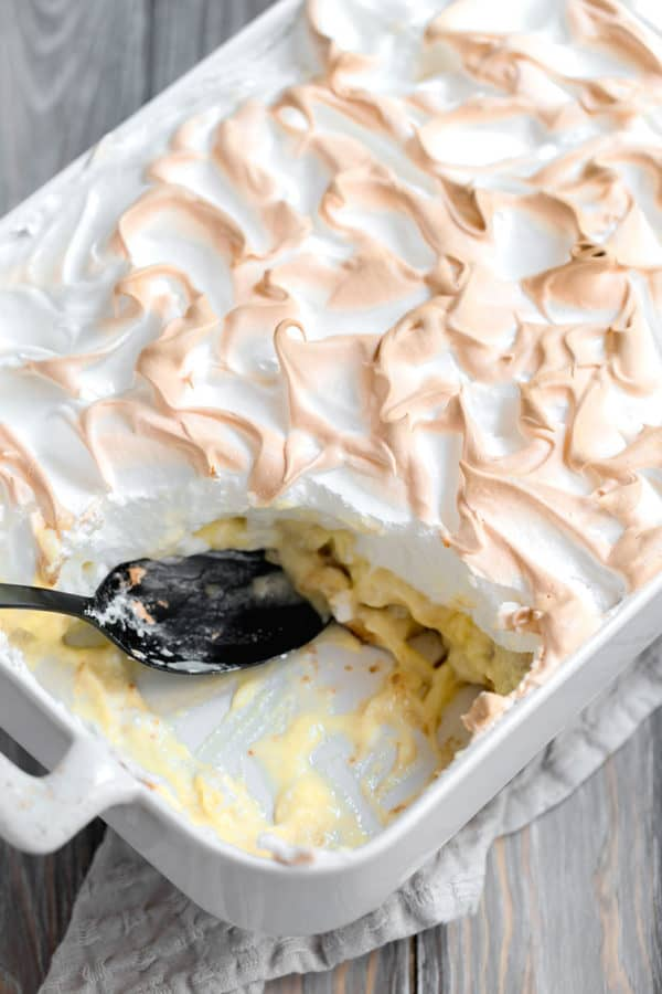 A pan of banana pudding with a corner scooped out.