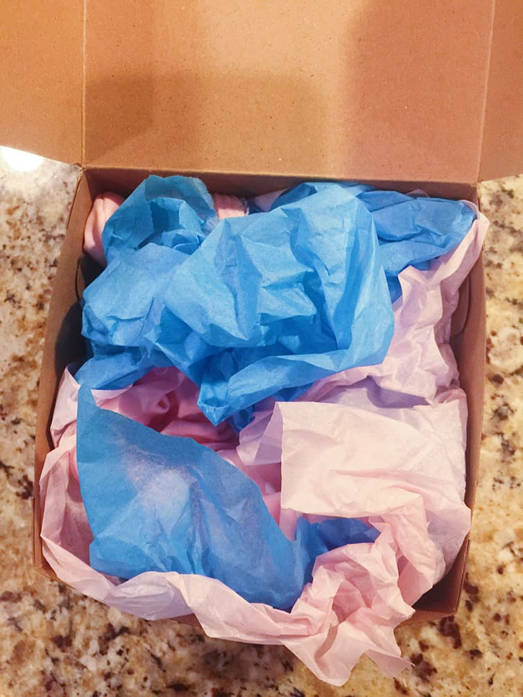 A box with blue and pink tissue paper for gender reveal.