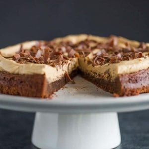 Brownie Cake with Cookie Butter Frosting on a serving platter with a slice missing.