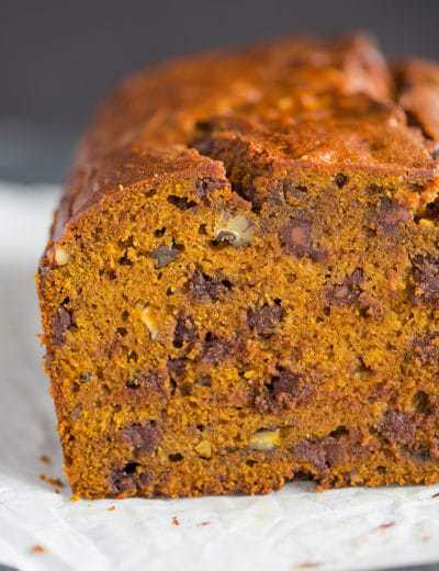 A cut loaf of pumpkin bread with chocolate chips and pecans.