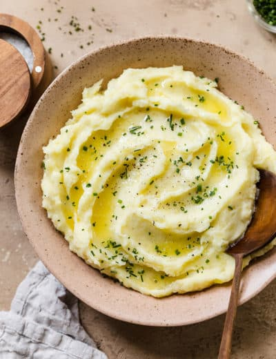 Mashed potatoes in a serving bowl with a wooden spoon.
