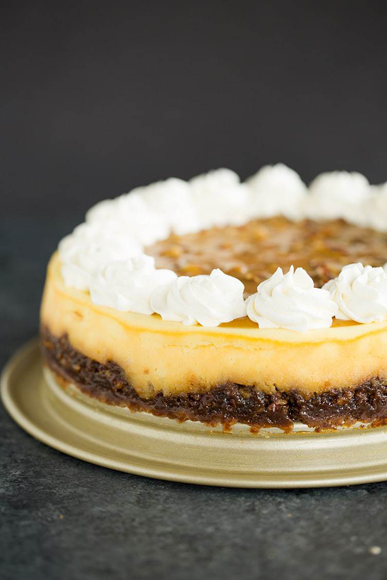 A pecan pie cheesecake with whipped cream rosettes on top.