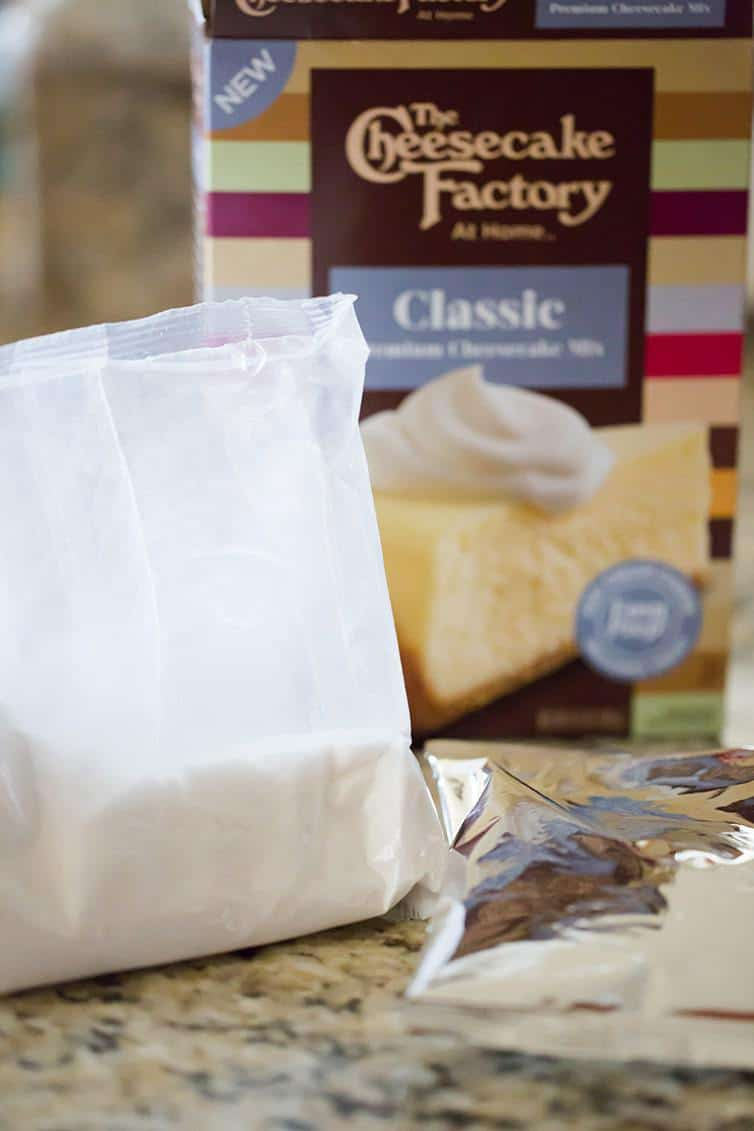 A box of The Cheesecake Factory At Home Cheesecake Mix with the pouches included.