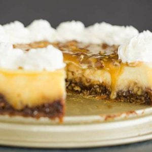 A whole pecan pie cheesecake with a slice removed.