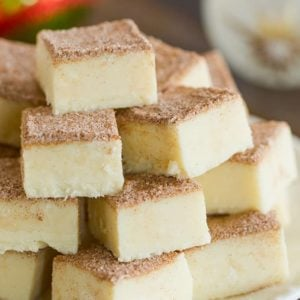 Squares of snickerdoodle fudge stacked on a white plate.