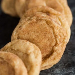 A display of snickerdoodle cookies on a dark serving plate.