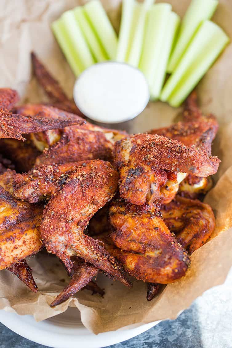 A basket of chicken wings with celery and ranch dressing.