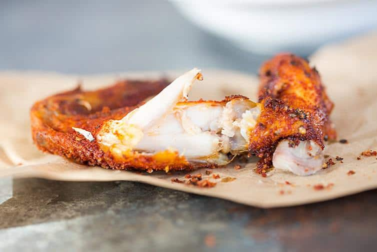 Close up of a baked chicken wing bitten into.