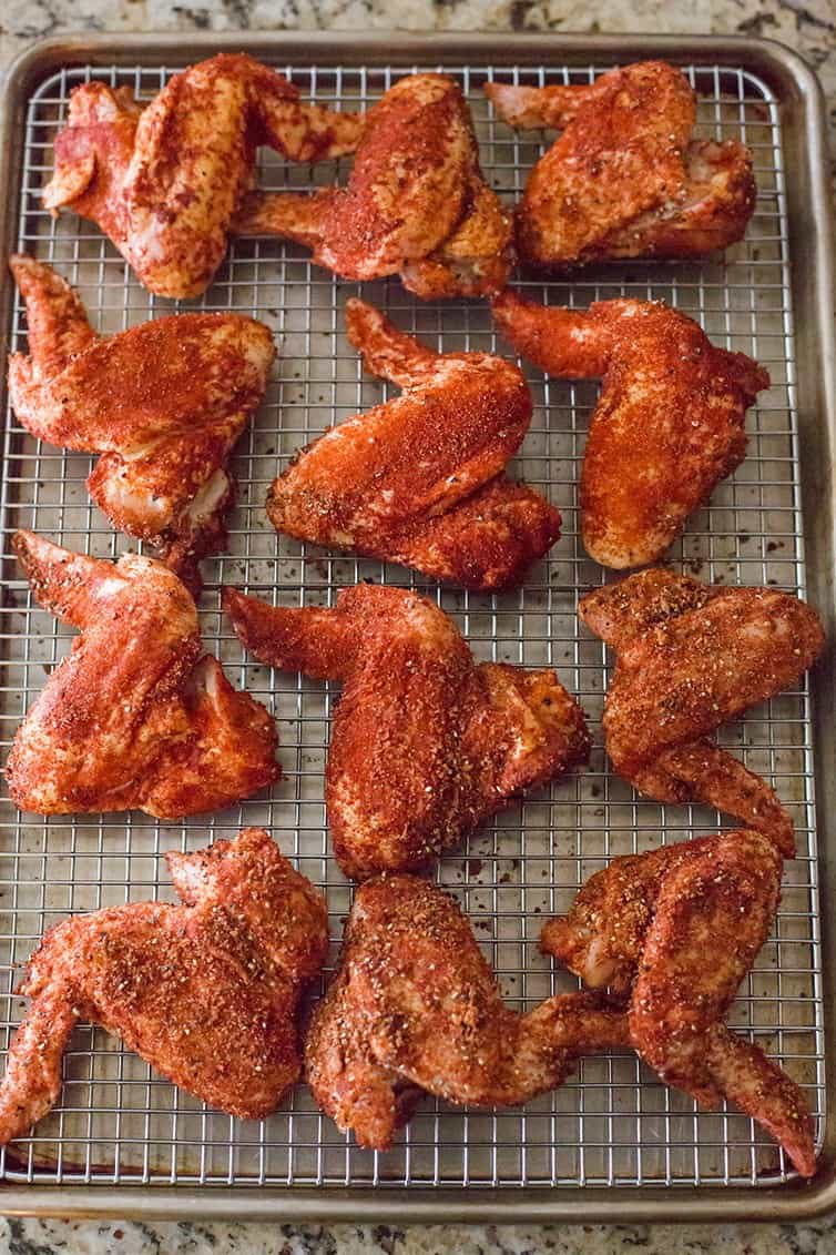 Uncooked seasoned chicken wings on a baking sheet.
