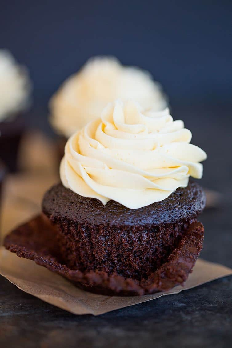 A chocolate cupcake with vanilla frosting with the paper wrapper pulled off halfway.