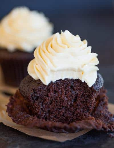 A chocolate cupcake with vanilla frosting with a bite taken out.