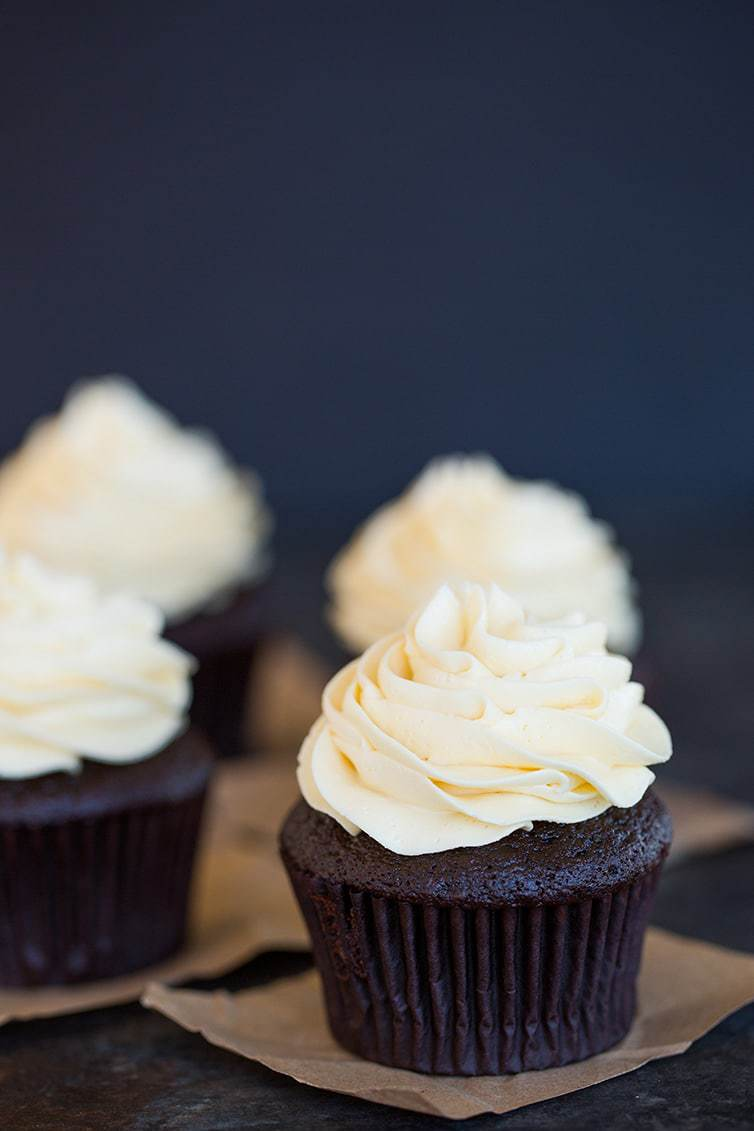 Four chocolate cupcakes with vanilla frosting on butcher paper squares.