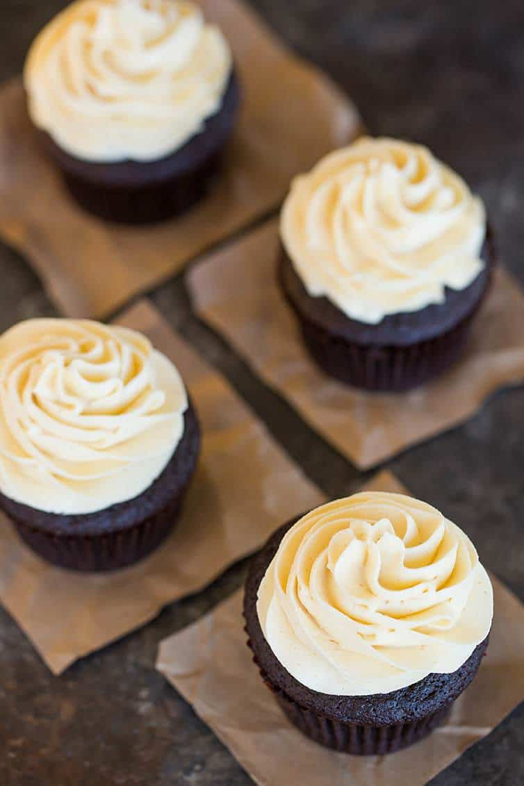 An overhead shot of four chocolate cupcakes with vanilla frosting.