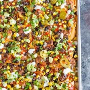 A sheet pan full of loaded nachos.
