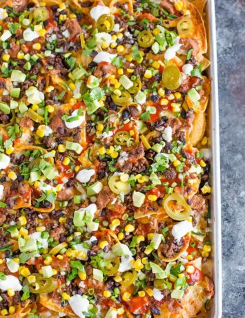 A sheet pan full of loaded nachos.