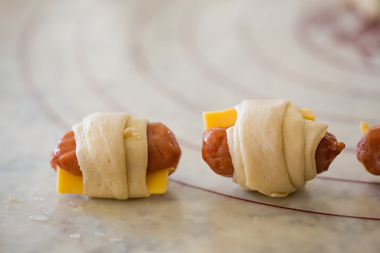 Mini hot dogs with cheese rolled up in crescent roll dough.
