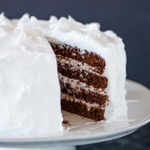 Devil's food cake on a cake stand with a slice of cake removed.