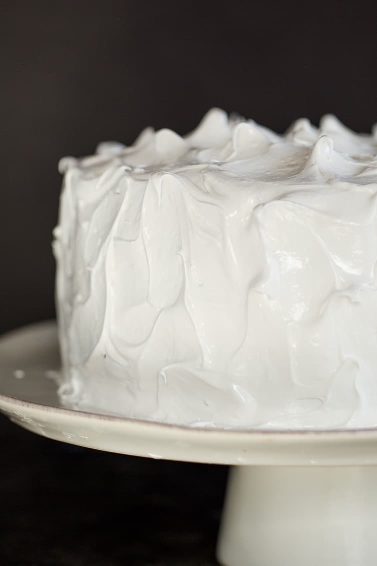 A devil's food cake covered in seven minute frosting on a cake stand.
