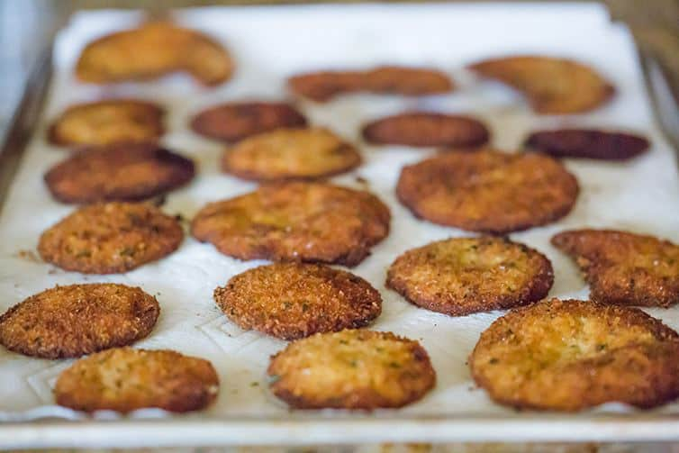 Fried eggplant slices draining on paper towels.