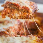 A slice of eggplant parmesan being lifted out of the pan.