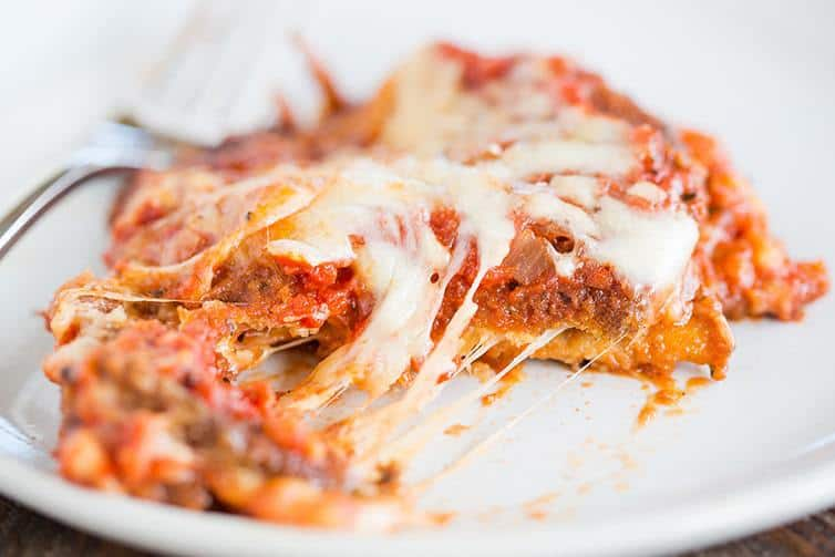 A slice of eggplant parmesan cut with melted cheese.