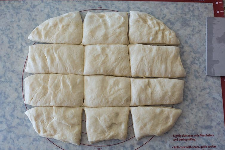 Milk Bread dough rolled out and cut into 12 pieces.