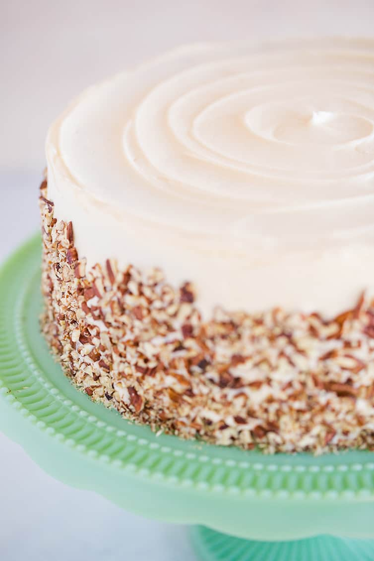 Assembled carrot cake with cream cheese icing and pecans around the outside.