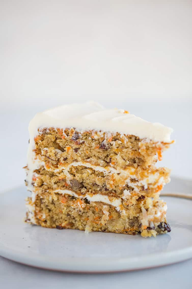 A slice of carrot cake filled and frosted with cream cheese frosting.