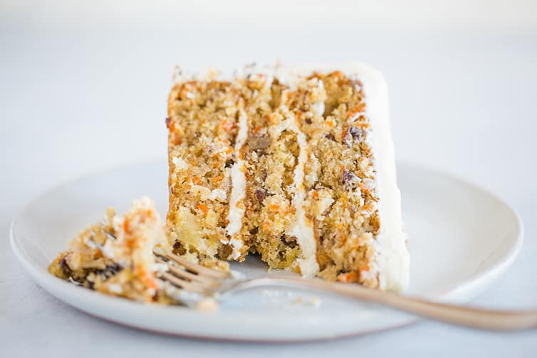 A slice of carrot cake on its side with a forkful taken out.