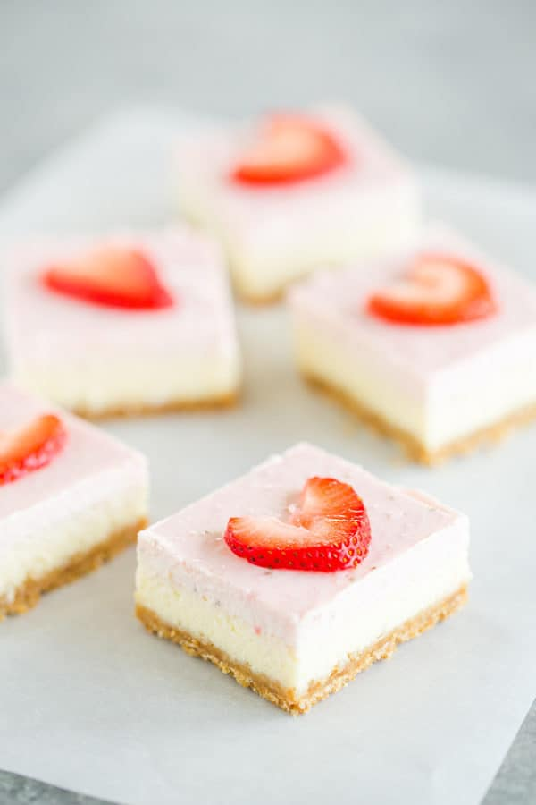 Five strawberry cheesecake bars on a piece of parchment paper.