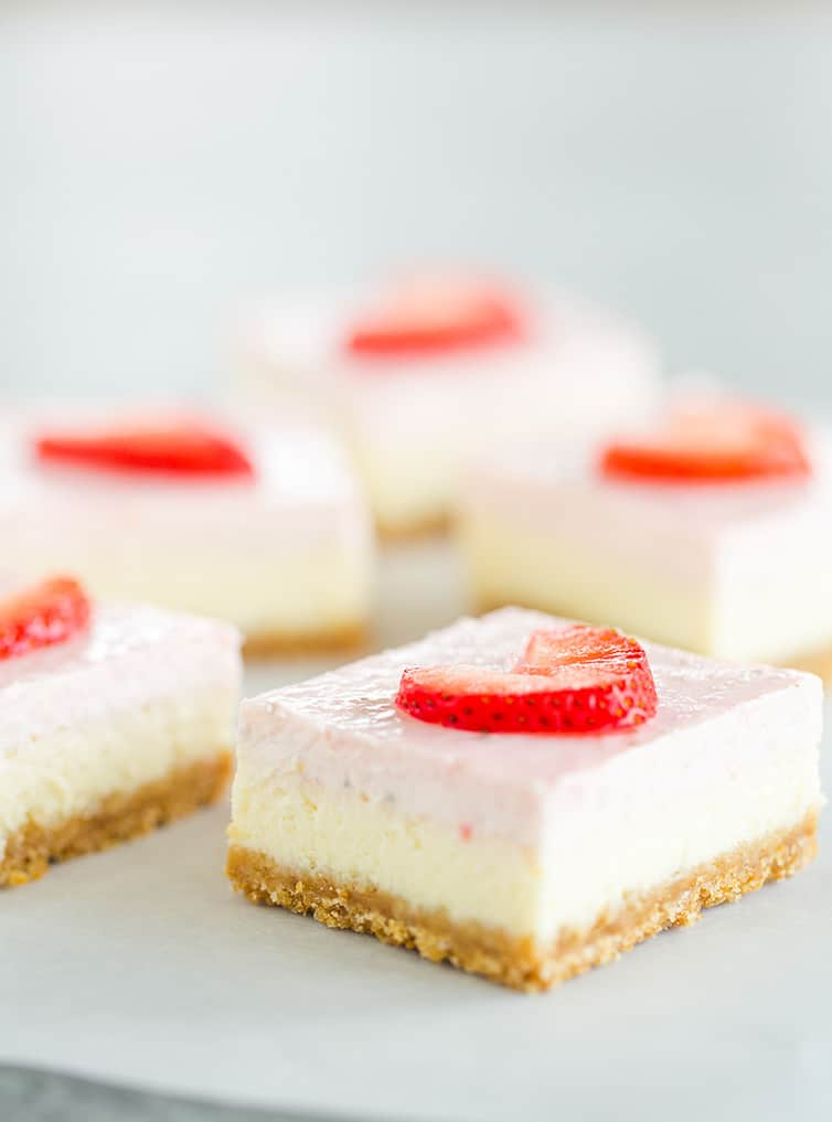 Multiple strawberry cheesecake bars sitting on parchment paper.