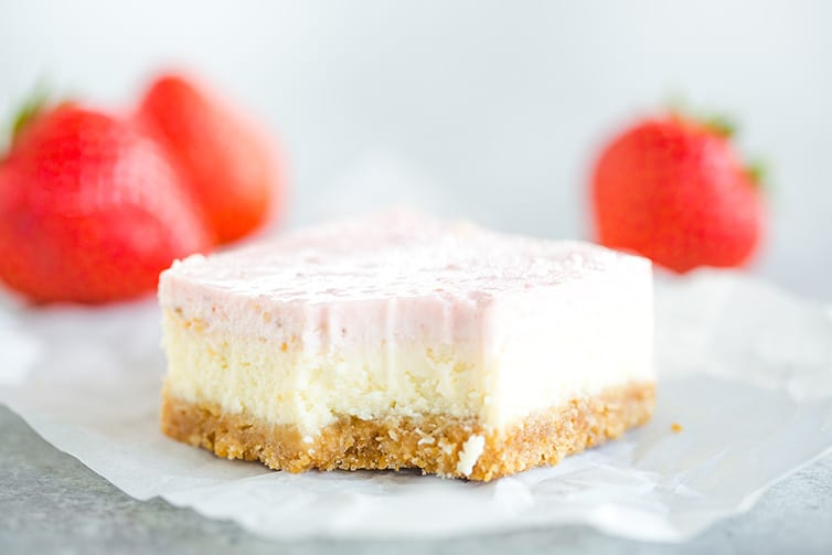A strawberry cheesecake bar with a bite taken out of it.