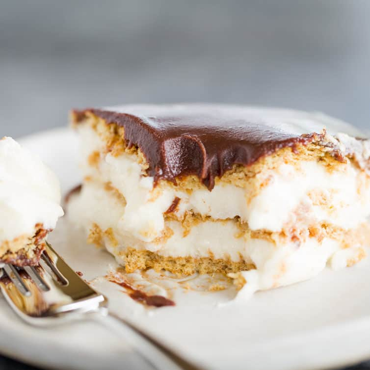 A piece of chocolate eclair cake with a forkful taken out of it.