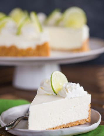 A slice of key lime cheesecake on a plate in front of the whole cheesecake.