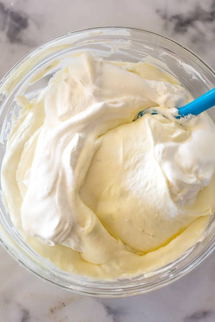 Folding heavy cream into the key lime cheesecake mixture.