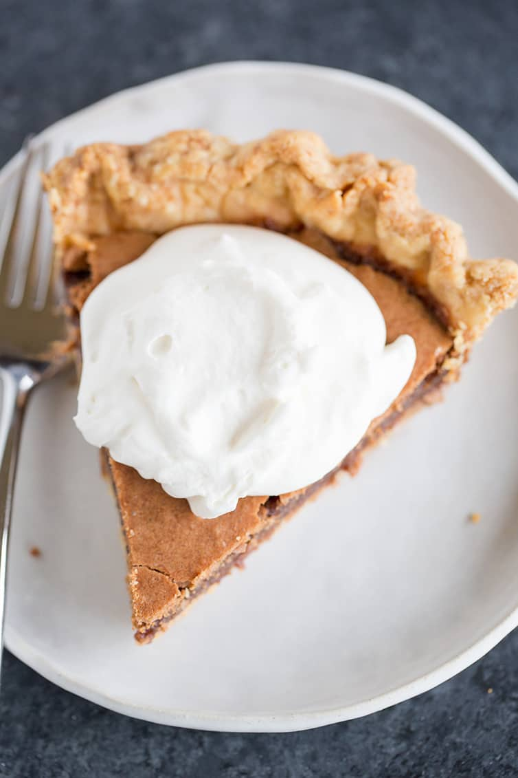 A slice of chocolate chess pie with whipped cream on top.