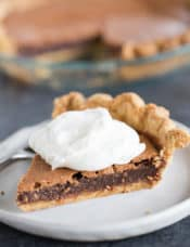 A slice of chocolate chess pie with whipped cream on top in front of the pie plate with the rest of the pie.