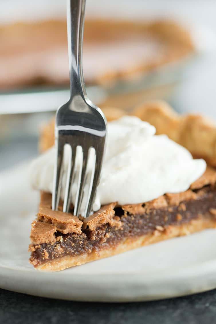 A slice of chocolate chess pie with a fork going through it.