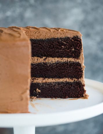 Three-layer chocolate cake on a serving platter with cut side exposed.