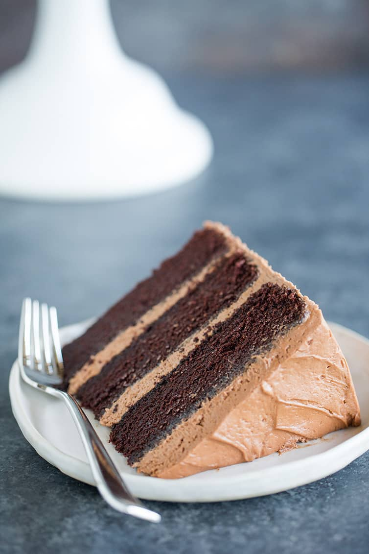 A slice of triple-layer chocolate cake on a plate.