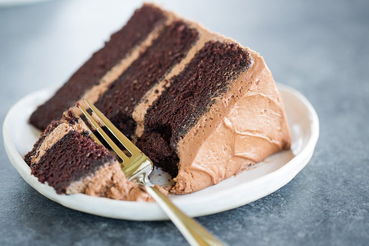 A slice of chocolate cake on a plate with a forkful taken out.