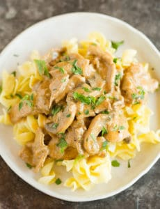 A plate of beef stroganoff over egg noodles.