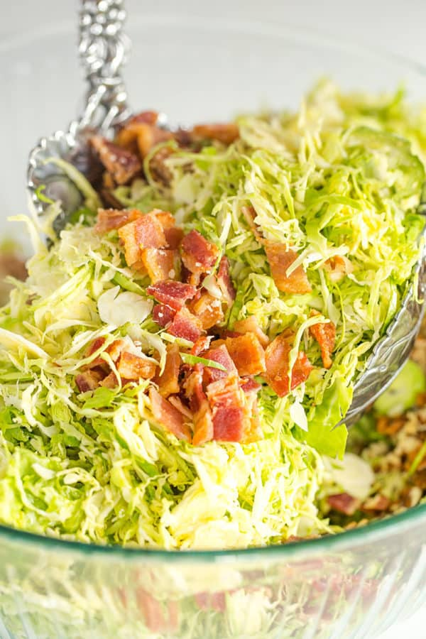 Tossing brussels sprouts salad with bacon, pecans and Parmesan cheese.