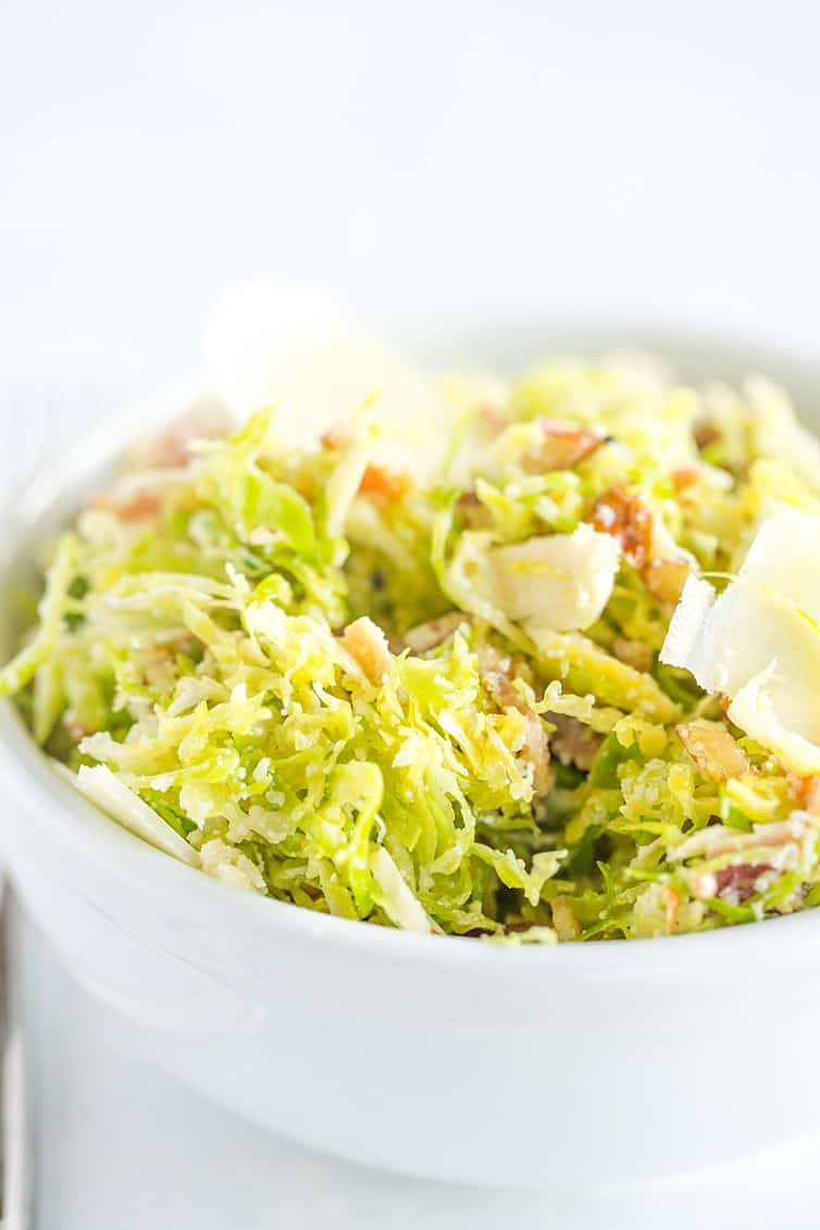 A bowl of Brussels sprouts salad with bacon, pecans and Parmesan cheese.