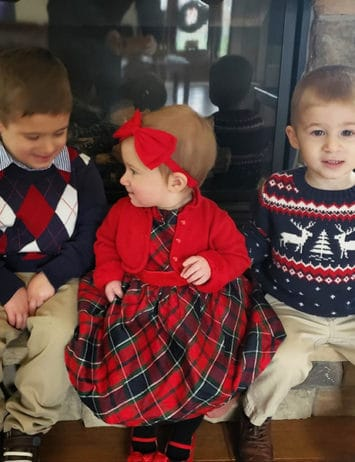 Two toddler boys and a baby girl sitting on the hearth of a fireplace.
