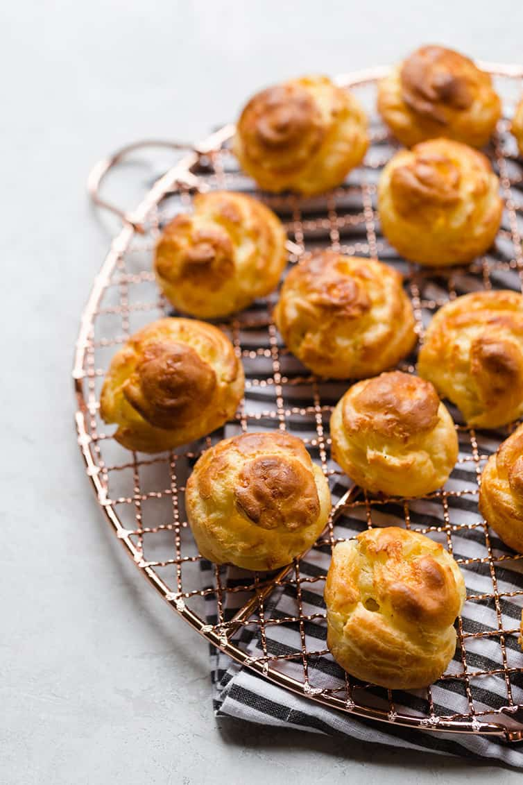 Baked gougeres on a round cooling rack.