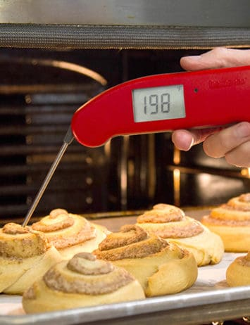 A tray of cinnamon rolls with an instant-read thermometer inserted into one of them.