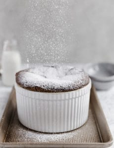 A chocolate souffle with powdered sugar being sprinkled on top.